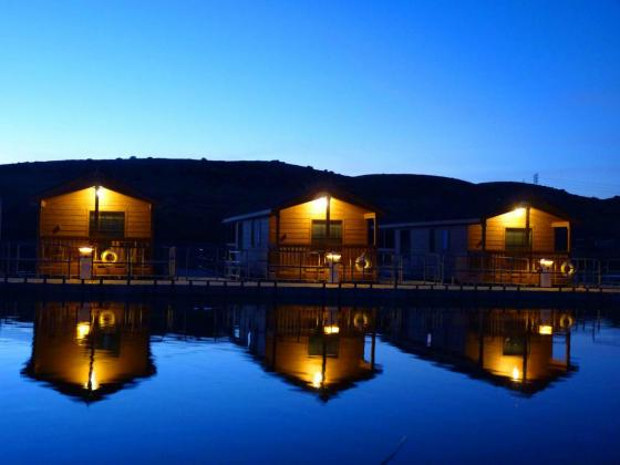 Floating Cabins at night, Seven others await on the waterfront