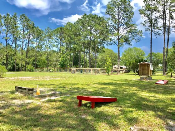 Outdoor activities including corn hole, volleyball, badminton, and basketball.